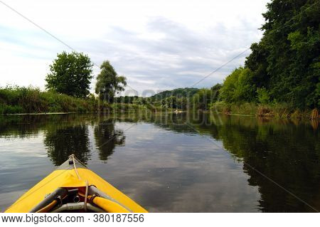Kayak Nose On The Background Of Picturesque Nature. Rowing In A Yellow Kayak In Summer Along The Tre
