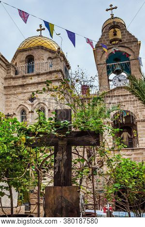Monastery of Gerasim of Jordan. Large cross made of wood. The inner monastery courtyard. Israel. The concept of pilgrimage, religious and photo tourism