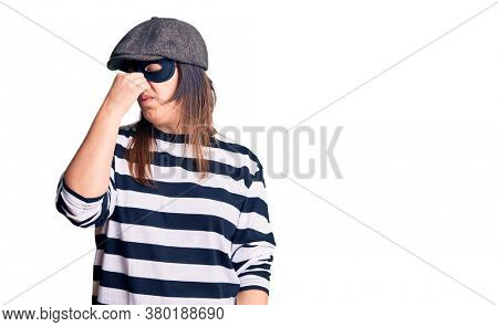Young beautiful brunette woman wearing burglar mask smelling something stinky and disgusting, intolerable smell, holding breath with fingers on nose. bad smell