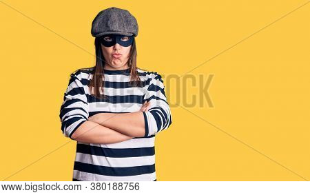 Young beautiful brunette woman wearing burglar mask skeptic and nervous, disapproving expression on face with crossed arms. negative person.