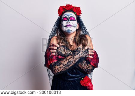 Young woman wearing day of the dead costume over white hugging oneself happy and positive, smiling confident. self love and self care