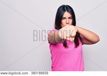 Young beautiful brunette woman wearing casual pink t-shirt standing over white background Punching fist to fight, aggressive and angry attack, threat and violence