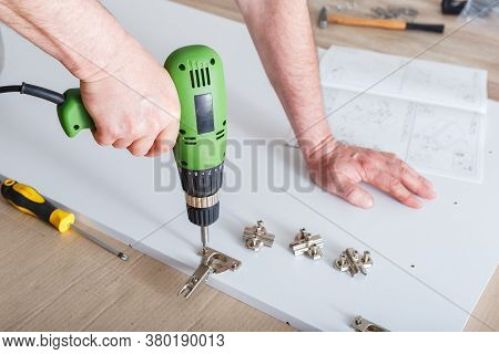 Furniture Assembly Using Drill. Male Hands Master Collects Furniture Using Tools Instrument Drill In