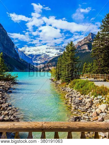 Glacial Lake Louise in Banff Park in Canada, Canadian Rockies. Pebble lake embankment and fence. Lake with azure water. The concept of ecological, active and photo tourism