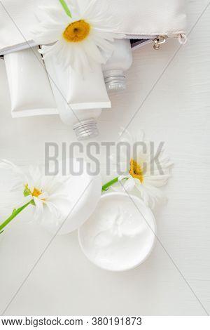 Moisturizer Skin Cream In White Jar With Chamomile Flowers. Mockup White Plastic Jar For Moisturizer