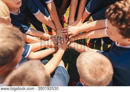 Happy Kids Sports Team Stacking Hands At The Field. Children Team Sports. Boys At Sports Camp Stacki