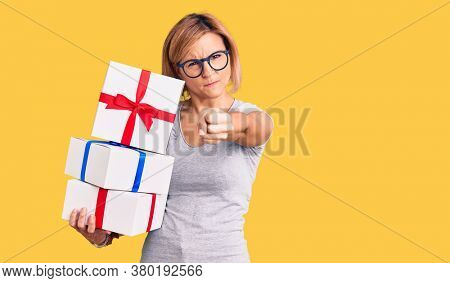 Young blonde woman wearing glasses holding gift annoyed and frustrated shouting with anger, yelling crazy with anger and hand raised