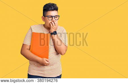Little boy kid holding book wearing glasses bored yawning tired covering mouth with hand. restless and sleepiness.