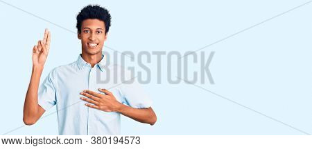 Young african american man wearing casual clothes smiling swearing with hand on chest and fingers up, making a loyalty promise oath