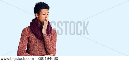 Young african american man wearing casual winter sweater and scarf bored yawning tired covering mouth with hand. restless and sleepiness.
