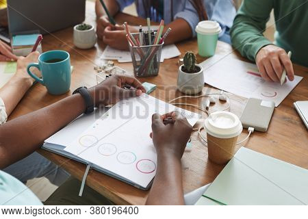 Close Up Of Multi-ethnic Group Of People Working Together At Cluttered Table With Cups, Mugs And Sta