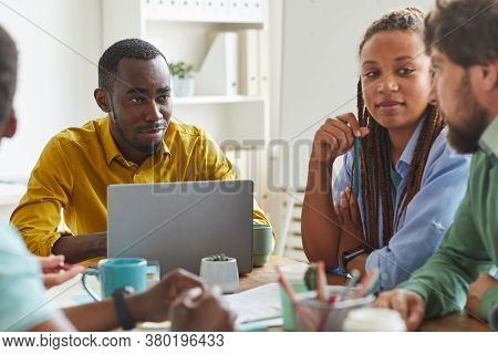 Portrait Of Creative African-american Man Using Laptop While Working On Team Project With Multi-ethn
