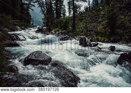 Powerful Mountain River Flow Through Forest. Beautiful Alpine Landscape With Azure Water In Fast Riv