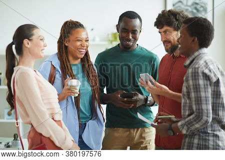 Waist Up Portrait Of Multi-ethnic Group Of People Dressed In Casual Wear And Laughing Cheerfully Whi