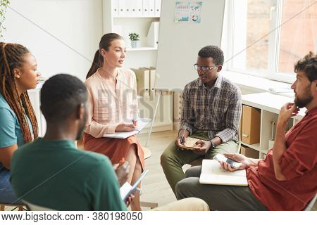 Multi-ethnic Group Of People Sitting In Circle While Discussing Strategy For Business Project In Off
