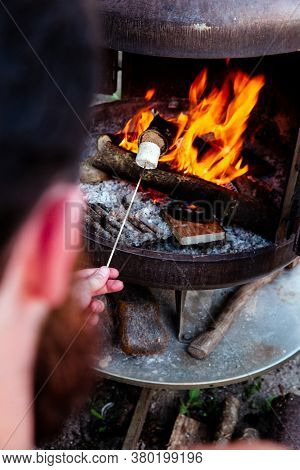 Person Roasting Over Fire Flames A Marshmallows Over Campfire At Night On A Summer Day, For Smores O