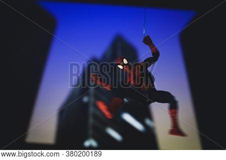 AUGUST 9 2020: Marvel comics superhero Spiderman swinging from a web at night - Hasbro action figure