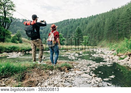 Young Couple Exploring Nature By The Mountain River