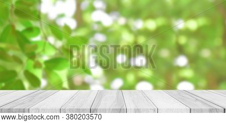 Empty White Wood Table Top With Blur Green Bokeh Background. For Display Or Montage Of Product Adver