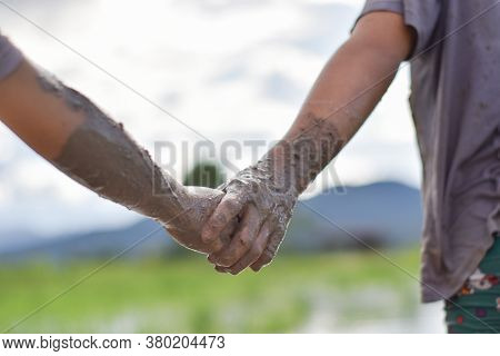 Hands Mud Clay Of Two Child Holding Each Other. Concept Of Mutual Assistance And Friendship
