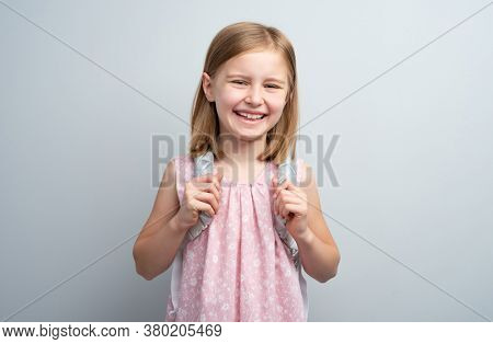 Smiling school girl with backpack on gray background