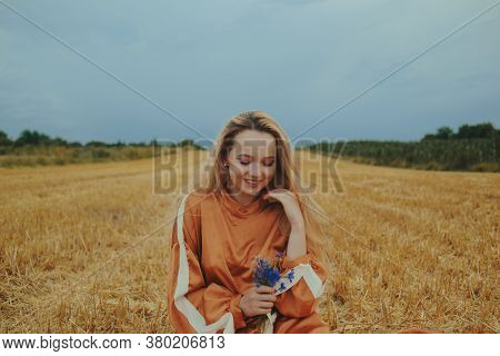 A Beautiful Girl In A Dress Sits On A Wheat Field. Fairytale Portrait Of A Blonde Outside The City.