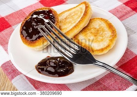 White Saucer With Small Homemade Pancakes And Chocolate Sauce, Fork On Checkered Napkin On Wooden Ta