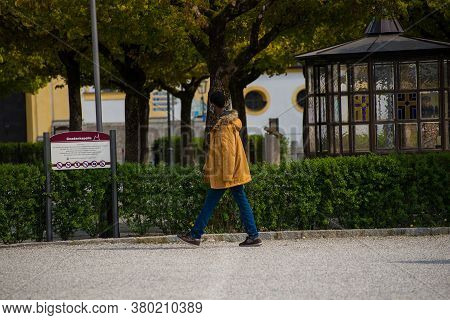 Altötting,germany-april 13,2020: A Man Wearing A Facemask Walks Past A Closed Church During The Coro