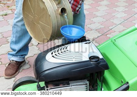 A Man Fueling A Lawn Mower. A Green Lawnmower. Gardening. Maintenance Of Equipment.