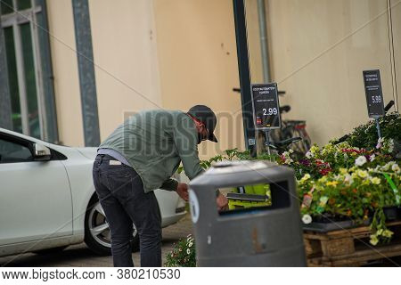 Neuoetting,germany-april 28,2020: A Man Wearing A Facemask Looks At Flowers Outside A Supermarket Af