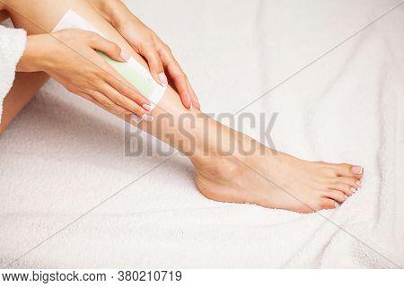 Waxing Woman Leg With Wax Strip At Beauty Spa