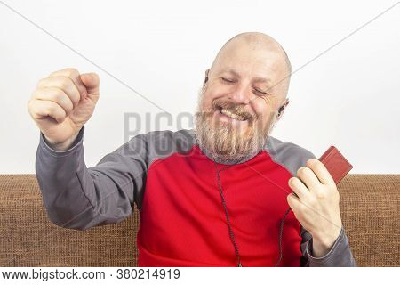 Bearded Man Likes To Listen To His Favorite Music At Home With An Audio Player In Small Headphones.