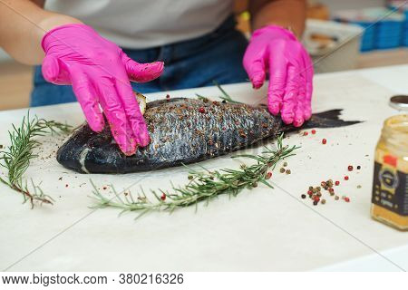 Women's Hands Are Preparing Dorada Fish For Dinner. Preparation For Cooking Fish Food.