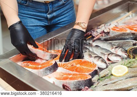 Female Hands Take Salmon Steak From Showcase. Fish Food At Shop, Close Up. Raw Fish Ready For Sale I