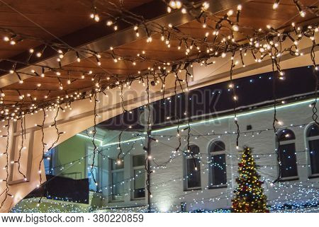 Christmas Decoration Of Buildings, Garlands With Light Bulbs On The Facade And Roof Of The Street Ma