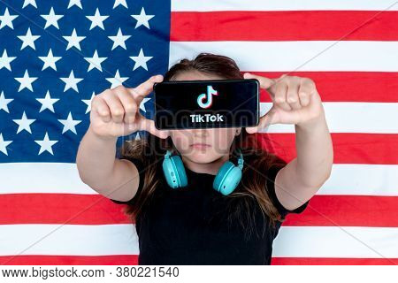 Top View A Teenager Holds A Smartphone With The Tiktok Logo And Against The Background Of The Americ