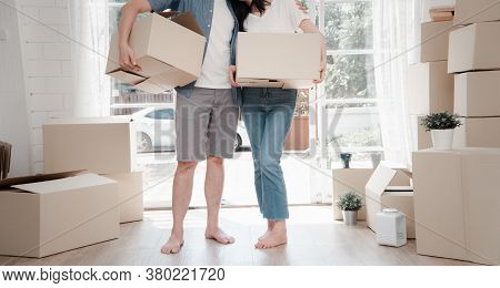 Happy Young Couple Carrying Cardboard Boxes And Standing In The Front Door Of A New House At Moving