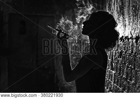 A Black And White Silhouette Portrait Of A Young Woman Smoking A Cigarette In A Mouthpiece