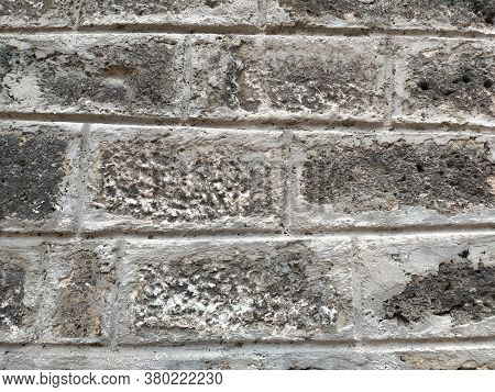 Weathered Aged Stone Masonry Of Old House. Ancient Brick Wall Background. Old Uneven Scratched Stone