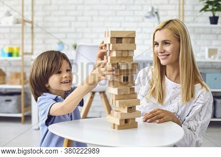 Little Boy Building Tower From Wooden Blocks With Mother At Home. Parent And Child Playing Board Gam