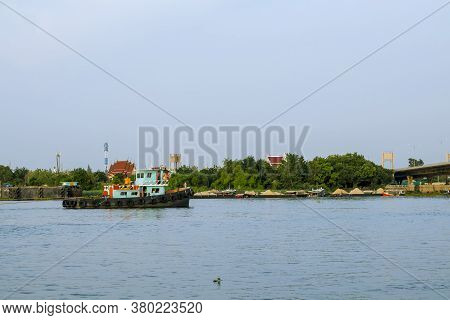 Scenery Of The Chao Phraya River With Boats And Temples In The Background In Thailand.