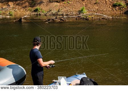 A Young White Guy With A Fishing Rod In His Hands Is Having A Good Time On Vacation. Spinning Fishin