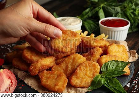 Female Hand Holds Nuggets Over The Wooden Background With Nuggets