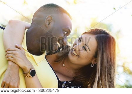 Close Up Outdoor Portrait Of Happy Multiracial Couple. Young Caucasian Woman Embracing Black Boyfrie