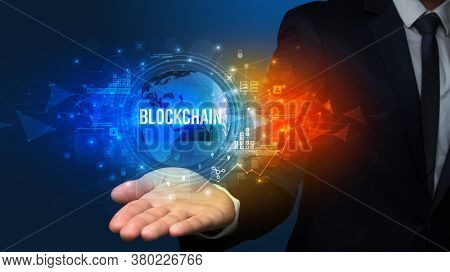 Elegant hand holding BLOCKCHAIN inscription, digital technology concept