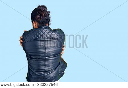 Young arab man wearing casual leather jacket hugging oneself happy and positive from backwards. self love and self care