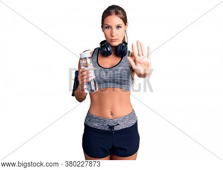 Young beautiful hispanic woman wearing sportswear holding water bottle with open hand doing stop sign with serious and confident expression, defense gesture