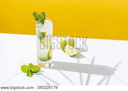 Fresh Mojito Cocktail With Lime And Mint In Highball Glass With Water Drops On White And Yellow Back