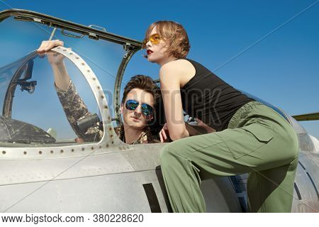 A beautiful girl and a handsome man pilots stand next to a fighter jet at the airfield. Military aircraft. Military fashion.