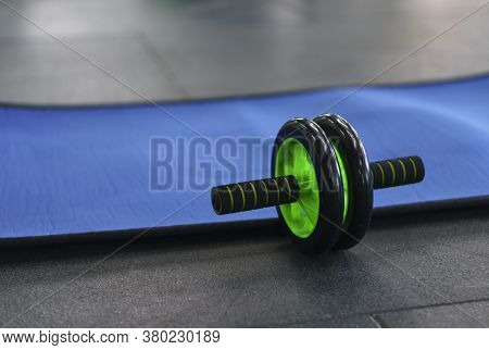 Press Roll On The Floor Near The Mat In The Fitness Room. The Development Of Abdominal Muscles With